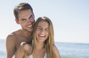 Athletic couple smiling at camera and hugging on the beach